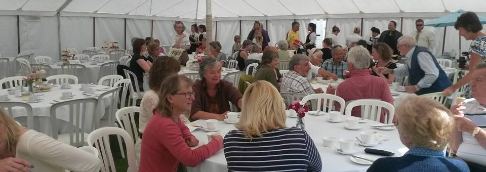 Photo of people have tea in a marquee.