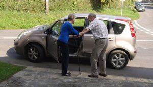 Lady helping elderly man into car