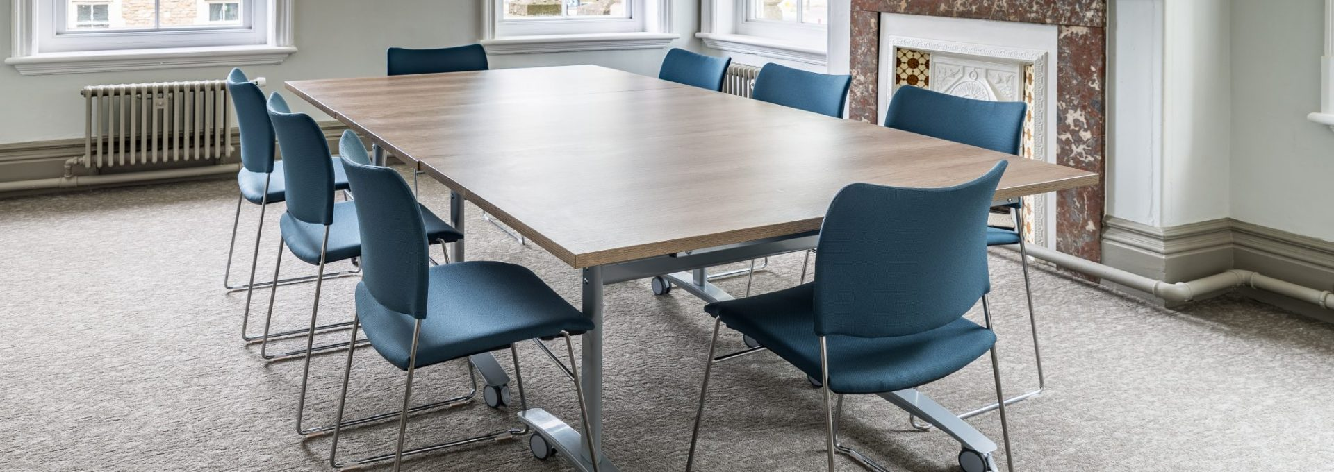 Photo of a large table with chairs around it at Frome Town Hall's meeting room.