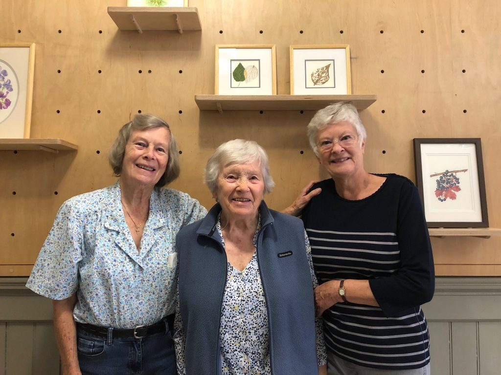Photo of the 'Late Bloomers' artists, Hazel, Margaret and Shirley in front of their artwork.