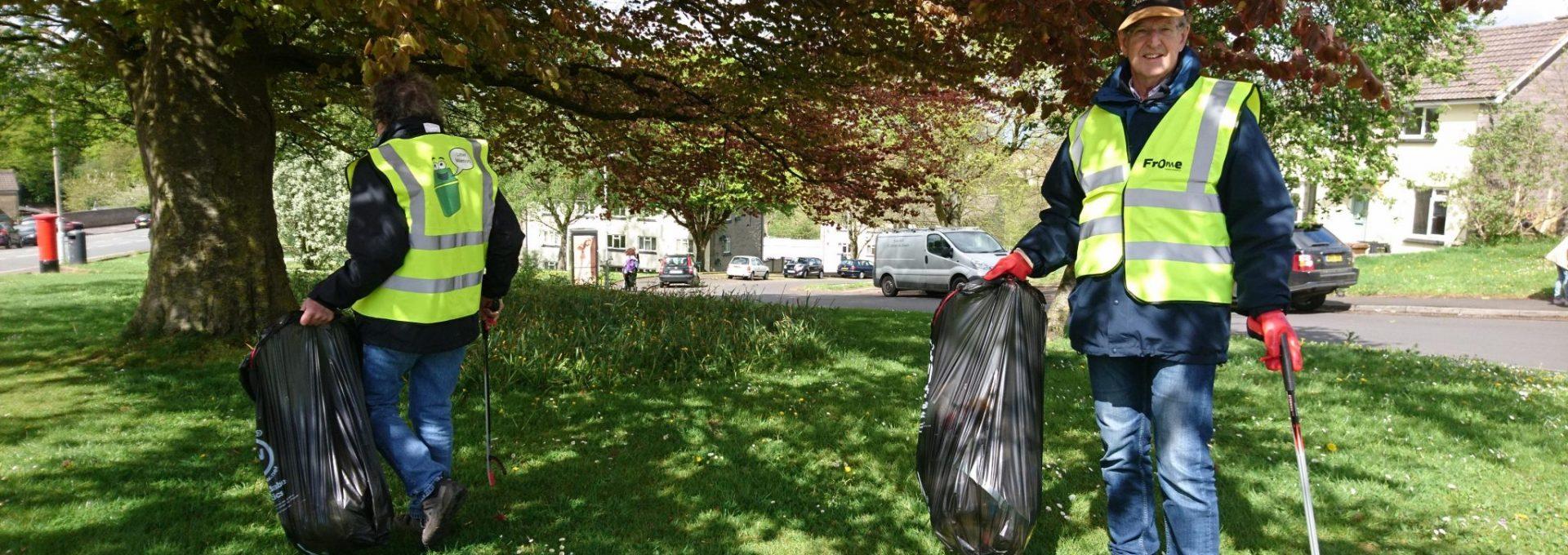 Man carrying bin bag and litter picker