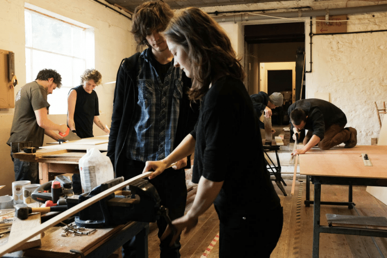 Two people in a wood workshop.