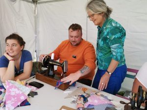 Councillor Sheila Gore watches man sewing bunting