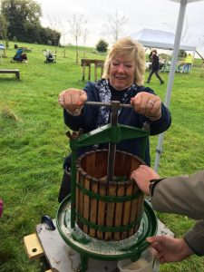 Deputy Mayor, Anita Collier, using an apple press at Apple Day 2019