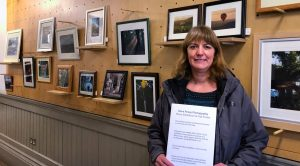 Lenka Grimes of Fair Frome standing in front of Dave Povey exhibition