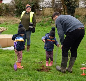 Photo of family planting trees