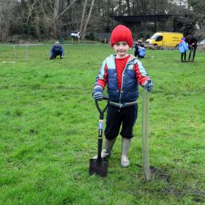 Photo of child holding a spade to plant a tree