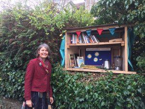 Annabelle Macfadyen standing next to a neighbourhood sharing box