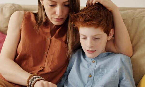 Woman on sofa with son looking at a tablet