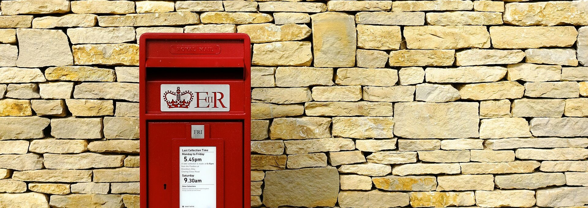 Red post box against brick wall