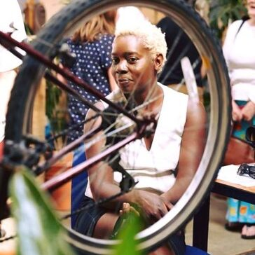Picture of a woman looking through the spokes of a wheel at the transition shed