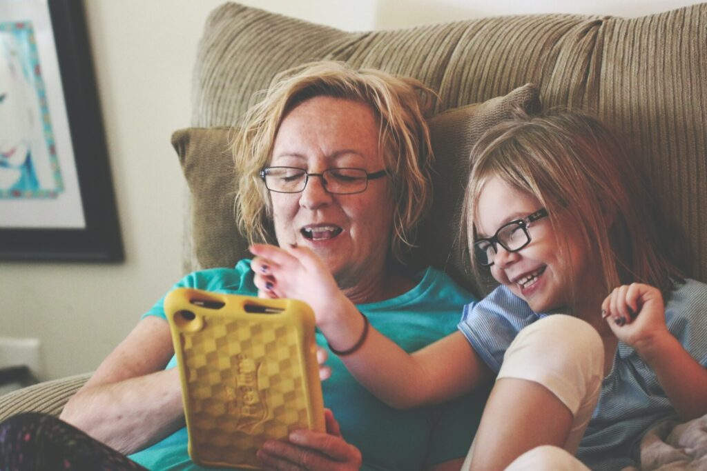 Woman and child sit on chair together and look at tablet