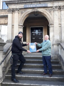 Deputy Mayor Andy Wrintmore receiving an award fromActive and In Touch's Dougie Brown outside Frome Town Hall