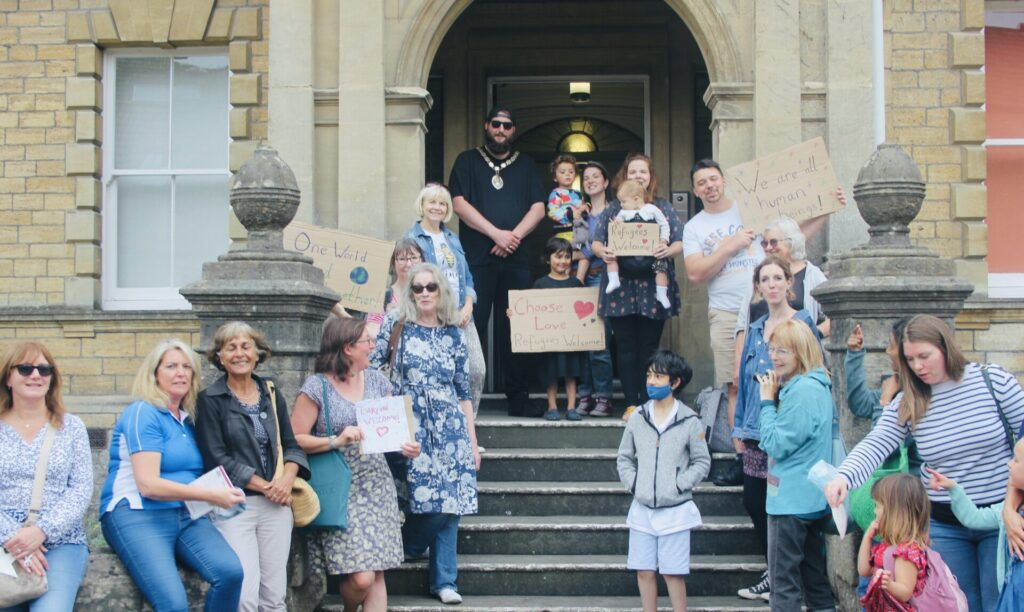 A group of peaceful demonstrators stand on Frome Town Hall steps with Mayor Andy Wrintmore