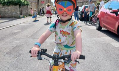 A young boy with a red mask sits on a yellow bike
